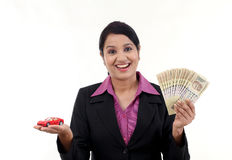 Cheerful business woman with money and toy car Stock Photo
