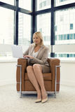 Cheerful business woman sitting in a chair. Working on laptop in Royalty Free Stock Photos