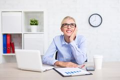 Cheerful business woman sitting in office and dreaming about som Stock Photography