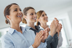 Cheerful business women applauding. Cheerful confident business women applauding and smiling, success and achievement concept stock image