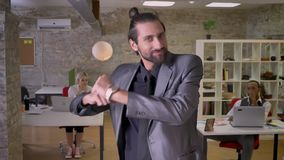 Cheerful businessman with beard is dancing in office, smiling, colleagues are watching at him, work concept, relax
