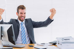 Cheerful businessman clenching fist computer at office desk Royalty Free Stock Photo