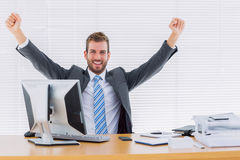 Cheerful businessman clenching fist at office desk Stock Photos
