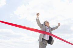Cheerful businessman crossing finish line against sky Royalty Free Stock Images