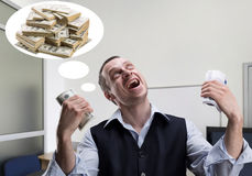 Cheerful businessman dreams about money. Cheerful businessman holds money and dreams in the office Royalty Free Stock Images