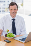 Cheerful businessman eating a salad on his desk. During the lunch time Stock Photos