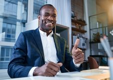 Cheerful businessman is expressing gladness. This is success. Low angle portrait of optimistic young confident african man is sitting at table with smile. He is royalty free stock photo