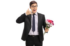 Cheerful businessman with flowers making a call me gesture Royalty Free Stock Photography