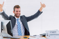 Cheerful businessman gesturing thumbs up at office desk Royalty Free Stock Photography
