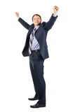 Cheerful businessman with hands raised in victory. Full length portrait of cheerful businessman with hands raised in victory, over white background Stock Image