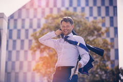 Cheerful businessman holding blazer and newspaper Royalty Free Stock Images