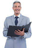 Cheerful businessman holding clipboard Royalty Free Stock Photography