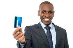 Cheerful businessman holding credit card. Young corporate guy showing his debit card Stock Image