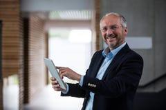 Cheerful businessman holding digital tablet Stock Photos
