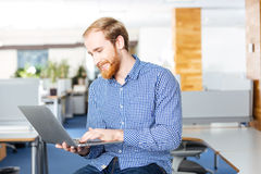 Cheerful businessman holding laptop and typing. Cheerful handsome bearded businessman holding laptop and typing Stock Photo