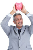 Cheerful businessman holding piggy bank above his head Stock Image