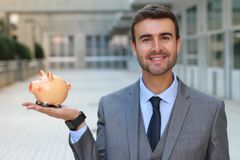 Cheerful businessman holding a piggybank royalty free stock image