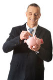 Cheerful businessman holding piggybank. Mature businessman putting a coin to piggybank Stock Image