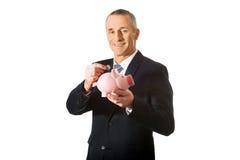 Cheerful businessman holding piggybank Stock Photos