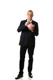 Cheerful businessman holding piggybank Royalty Free Stock Photo