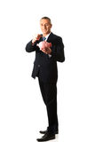 Cheerful businessman holding piggybank. Mature businessman putting a coin to piggybank Royalty Free Stock Images