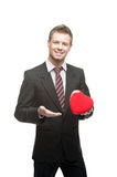 Cheerful businessman holding red heart Stock Photo