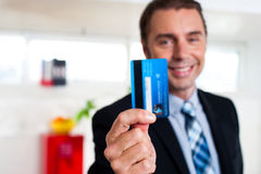 Cheerful businessman holding up his credit card Royalty Free Stock Photography