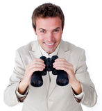 Cheerful businessman looking through binoculars. Isolated on a white background Stock Photos