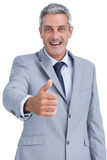 Cheerful businessman looking at camera reaching for handshake Stock Image