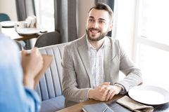 Cheerful businessman making order in restaurant. Happy positive handsome young businessman sitting at table with plate and smiling to waitress while making order stock photo