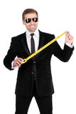 Cheerful businessman measuring the length of business success wi. Th tape measure. Isolated on white background Royalty Free Stock Photo