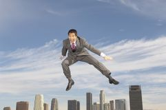 Cheerful Businessman In Midair. Full length of a cheerful Chinese businessman in midair Stock Photography