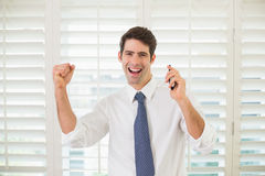 Cheerful businessman with mobile phone clenching fist in office Stock Image