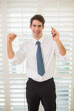 Cheerful businessman with mobile phone clenching fist in office Stock Photography