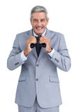 Cheerful businessman observing with binoculars Royalty Free Stock Image