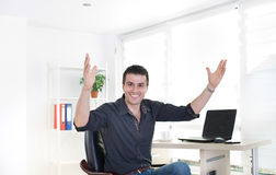 Cheerful businessman in office with raised arms. Enthusiastic young businessman sitting at office desk with laptop and raising arms in air. Achievement and Stock Image
