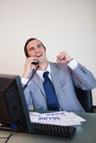 Cheerful businessman on the phone. Raising hand stock image