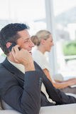 Cheerful businessman on the phone with his colleague working on Stock Images