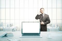 Cheerful businessman on phone in office. Cheerful businessman talking on phone in office with blank white laptop computer, coffee cup, paperwork, books and city Royalty Free Stock Images