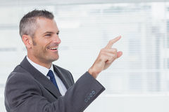 Cheerful businessman pointing while looking away Stock Photo