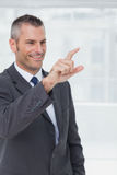 Cheerful businessman pointing and looking straight ahead Stock Photos