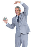 Cheerful businessman pointing out alarm clock Royalty Free Stock Photo