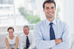 Cheerful businessman posing while his colleagues are working Royalty Free Stock Image