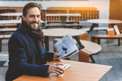 Cheerful businessman resting in cafe outside Stock Photo