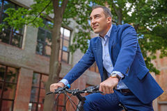 Cheerful businessman riding a bicycle. Happy man is cycling in city. He is looking forward with aspiration. Worker is smiling Stock Photos
