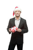 Cheerful businessman in santa hat holding red gift Royalty Free Stock Photo