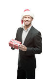 Cheerful businessman in santa hat holding red gift Stock Photos