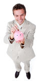 Cheerful businessman saving money in a piggy-bank Royalty Free Stock Photo