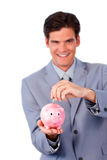 Cheerful businessman saving money in a piggy-bank Stock Images