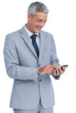 Cheerful businessman sending text message Stock Photography